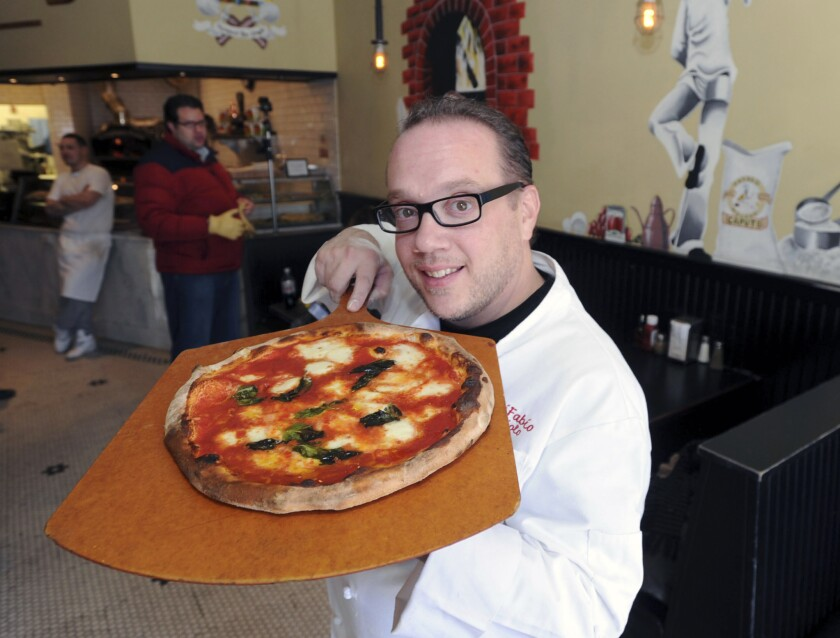 """FILE - In this Jan. 29, 2014 file photo, Bruno DiFabio displays a Margherita pizza at ReNapoli Pizzeria & Chicago Italian Beef in Old Greenwich, Conn. Celebrity pizza chef Bruno DiFabio has been sentenced to 30 days in prison for tax evasion. Known as """"Lord of the Pies,"""" DiFabio was sentenced Thursday, May 6, 2021 in federal court in Bridgeport, Connecticut. (Bob Luckey/Hearst Connecticut Media via AP, File)"""