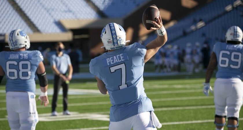 """North Carolina quarterback Sam Howell (7) has replaced his last name with 'Peace"""" on the back of his game jersey as he warms up for the Tar Heels' game against Notre Dame on Saturday, November 27, 2020 at Kenan Stadium in Chapel Hill, N.C. Several players has done the same, choosing other messages for this particular game. (Robert Willett/The News & Observer via AP)"""