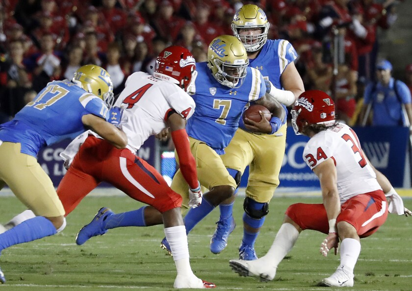 UCLA quarterback Dorian Thompson-Robinson (7) looks for room to run against Fresno State in the first quarter on Saturday at the Rose Bowl.