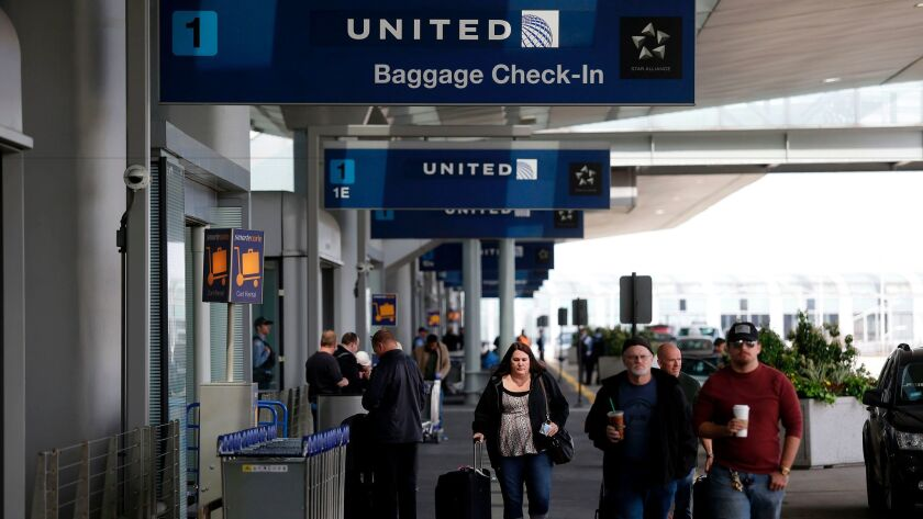 Travelers walk outside the United Airlines terminal at O'Hare International Airport on April 12, 201