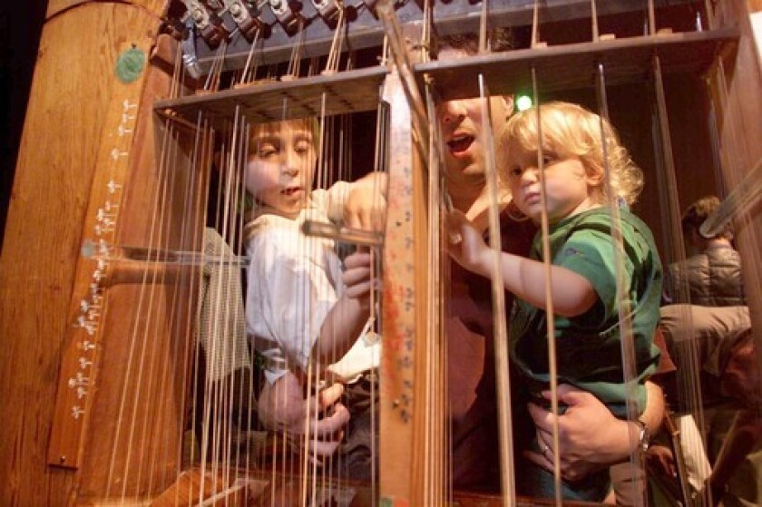 HAVE A GO AT IT: UCLA professor David Lefkowitz lets children Adam and Talia take a playing Harry Partch's Kithara.