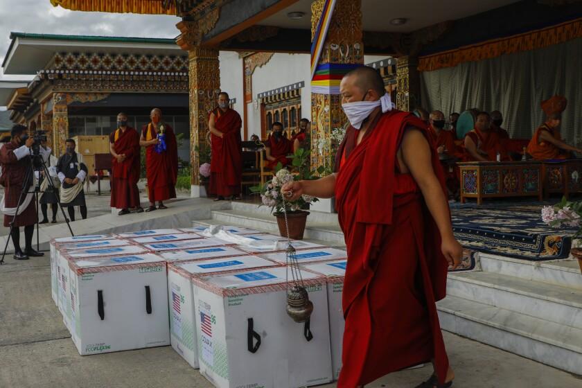 La foto distribuida por UNICEF muestra a monjes del organismo monástico de Paro realizar un rito cuando 500.000 dosis de la vacuna de Moderna contra el COVID-19 llegan desde Estados Unidos al Aeropuerto Internacional de Paro, Bhutan, 12 de julio de 2021. (UNICEF via AP)