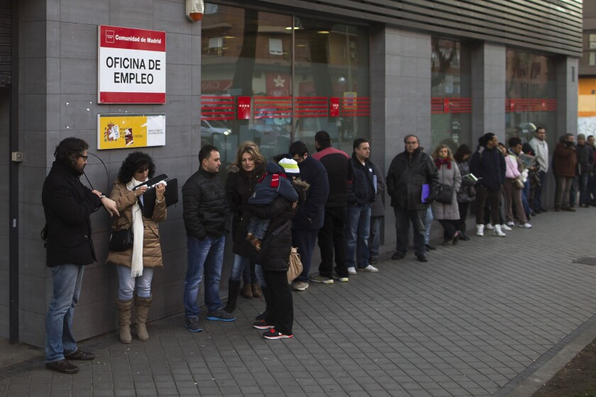 People wait in line outside an unemployment registry office in Madrid on Thursday. Spain's unemployment rate remained stuck at 26% in the fourth quarter as the economy expanded but not enough to trigger job growth, according to a pair of government reports issued Thursday.