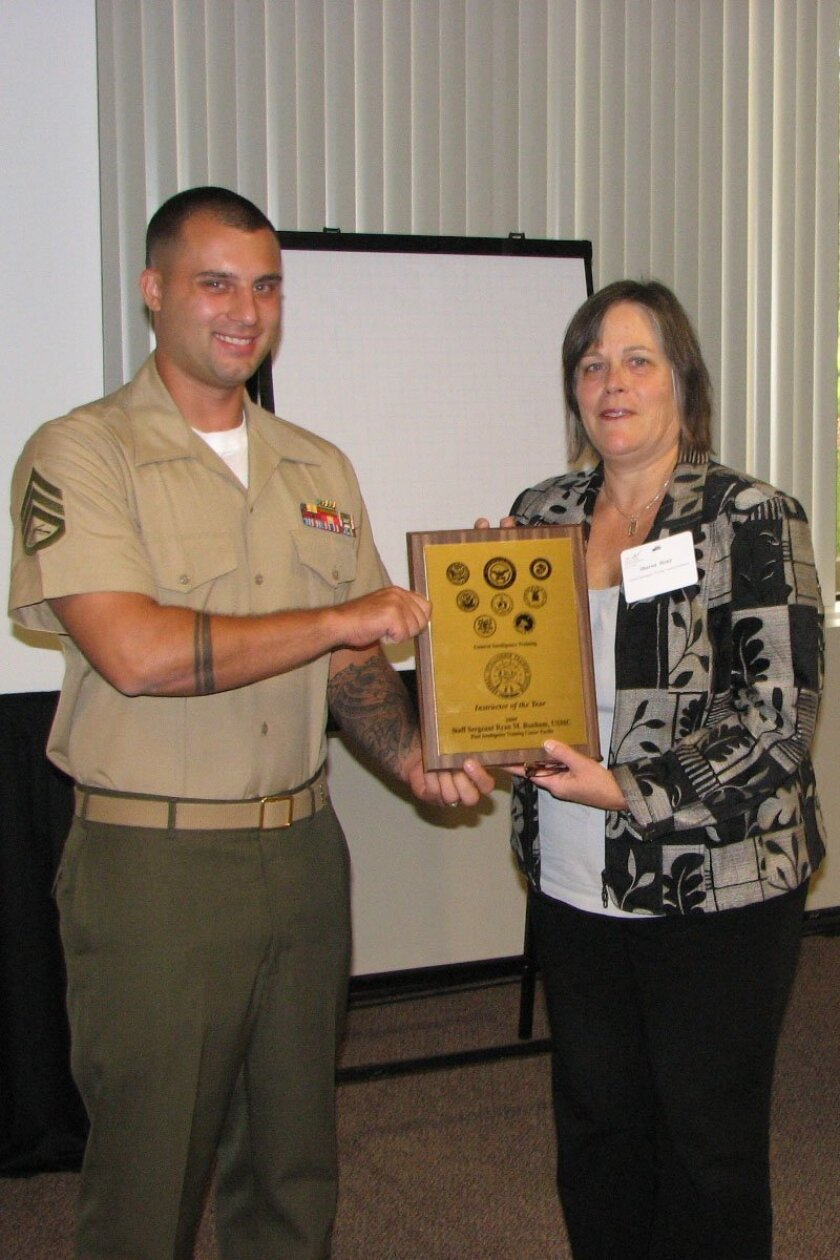 Staff Sgt. Ryan Bonham receives the Defense Intelligence Agency Instructor of the Year award from Sharon Houy, DIA Chief of Staff, at a conference Oct. 25 in Virginia.