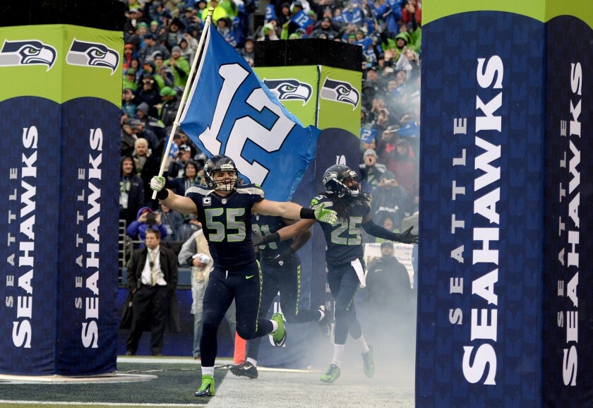 Seattle linebacker Heath Farwell runs out of the Seahawks' tunnel with the 12th Man flag before an NFC Divisional playoff game against the New Orleans Saints at CenturyLink Field on Jan. 11.