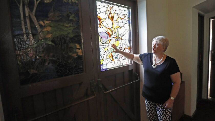 Joy Price, pastor of Christ Church by the Sea in Newport Beach, surveys vandalism damage to stained-glass windows at the main entrance to the church's sanctuary.