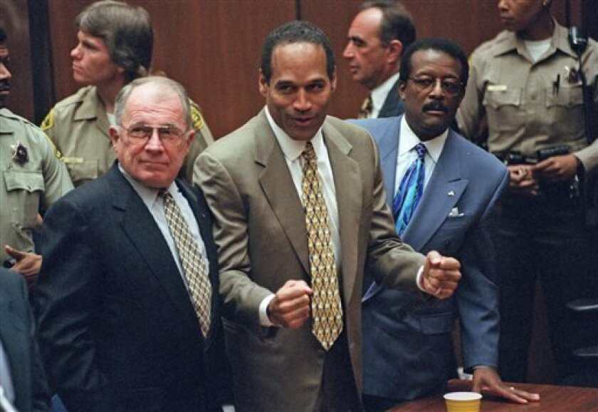 FILE - In this Oct. 3, 1995 file photo, O.J. Simpson, center, reacts as he is found not guilty of murdering his ex-wife Nicole Brown and her friend Ron Goldman, as members of his defense team, F. Lee Bailey, left, and Johnnie Cochran Jr., right, look on, in court in Los Angeles. The return of O.J. Simpson to a Las Vegas courtroom next Monday, May, 13, will remind Americans of a tragedy that became a national obsession and in the process changed the country's attitude toward the justice system,
