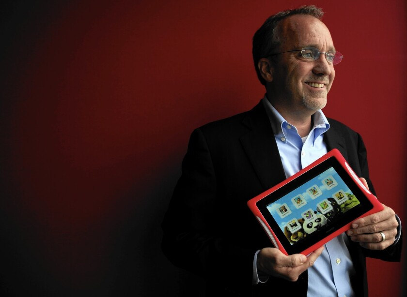 """Fuhu CEO Jim Mitchell holds one of the El Segundo children's tablet maker's products in March 2014. He said Fuhu expects """"to be able to satisfy ongoing obligations"""" with its proposed sale to Mattel."""