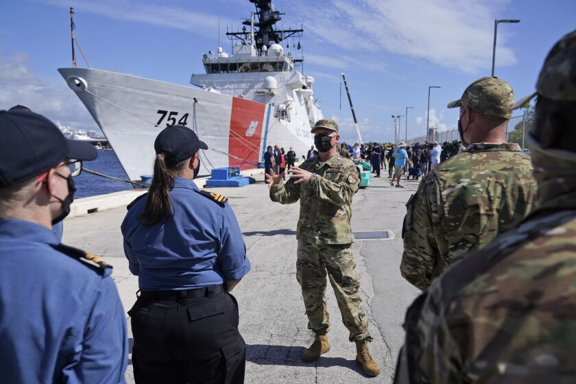 With the U.S. Coast Guard Cutter James behind him, Lt. Gen. Andrew Croft, center, Military Deputy Commander, U.S. Southern Command, speaks with Canadian and American Coast Guardsmen, Thursday, Aug. 5, 2021, at Port Everglades in Fort Lauderdale, Fla. The Coast Guard offloaded drugs worth more than $1.4 billion. The agency announced Thursday that the crew of the Cutter James offloaded about 59,700 pounds of cocaine and approximately 1,430 pounds of marijuana. (AP Photo/Wilfredo Lee)