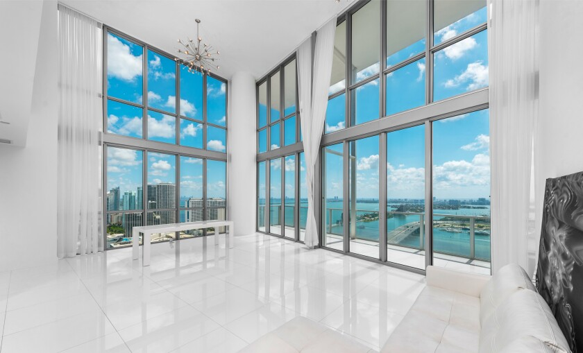 The corner-unit condo takes in sweeping city and ocean views across 3,850 square feet of sleek living spaces.