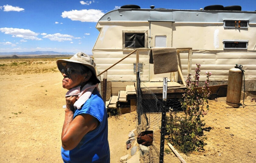 "Cynthia Dixon outside her trailer in Fruitland, N.M. Dixon lives near a coal mine and the Four Corners electrical plant, which she blames for health problems. She wants to leave. ""But where can I go?"""