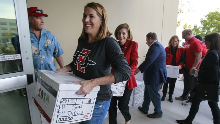 SDSU West supporter Kathleen Czech, left, and San Diego City Council member Barbara Bry, center, help carry boxes in January holding more than 106,000 signatures of San Diego voters,