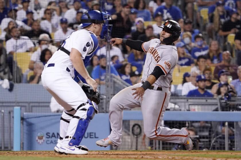 San Francisco Giants' Donovan Solano scores on a double by Thairo Estrada as Dodgers catcher Will Smith waits for the ball.