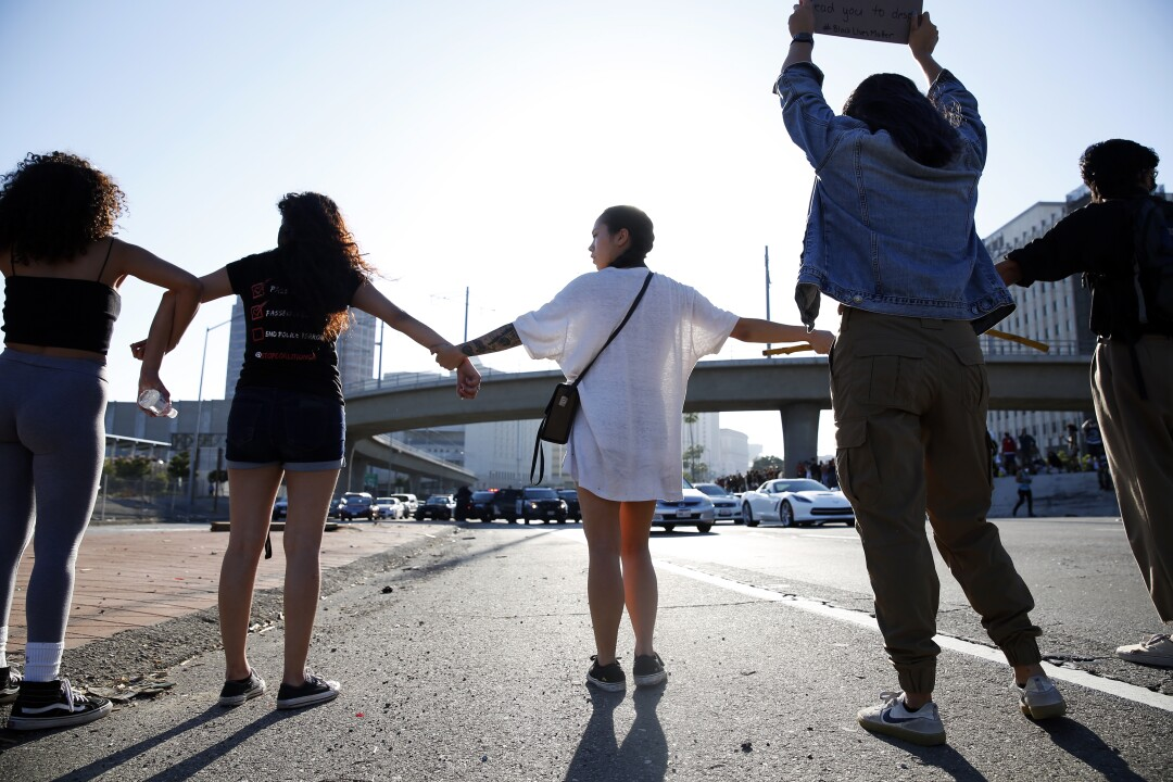Protesters link hands across the 101 Freeway in downtown Los Angeles in a demonstration over the death of George Floyd in Minneapolis.