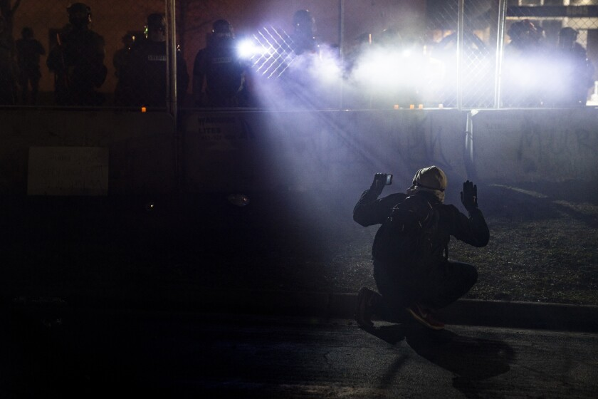 Police shine lights on a demonstrator with raised hands during a protest.