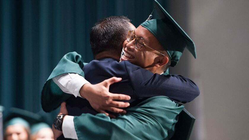Board pf Regents member Francis Largos gives a hug to his son, Paolo, before presenting him with his