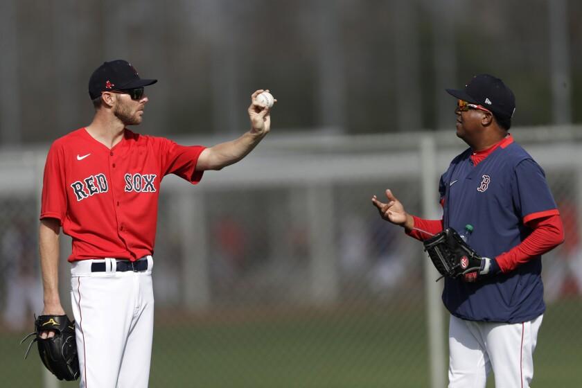 Boston Red Sox starting pitcher Chris Sale, left, talks with Pedro Martinez during spring training baseball camp Wednesday, Feb. 19, 2020, in Sarasota, Fla. (AP Photo/John Bazemore)