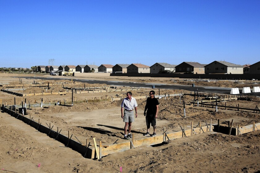 Michael Howarth, left, and Allen Colantuono of Sorrento Homes survey their company's new residential development project in Hesperia.
