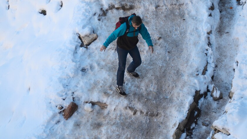 With snow and ice still abundant on a March day at the Grand Canyon's South Kaibab Trail, this sneaker-wearing hiker may be wishing he'd slipped on a pair of crampons for traction.