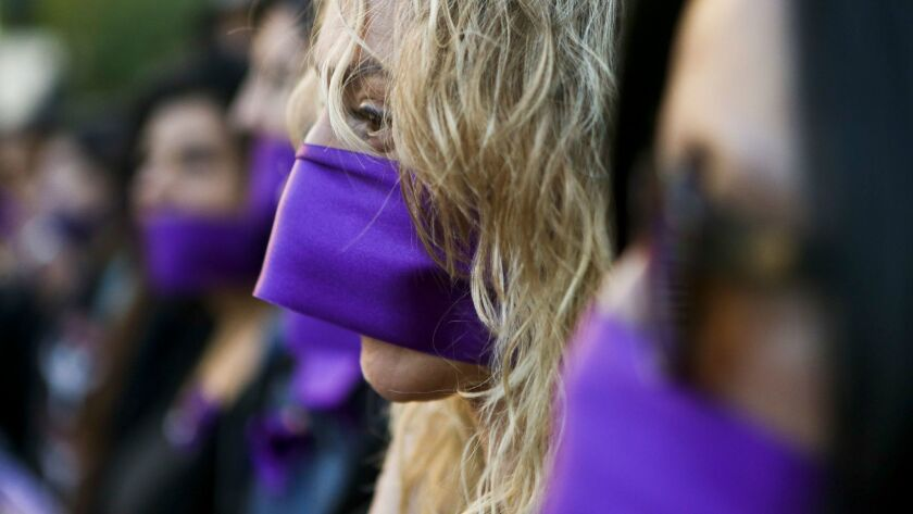 """Santiago, Chile: Women wear purple ribbons over their mouths during the """"Todas en Silencio"""" demonstration in front of La Moneda presidential palace."""