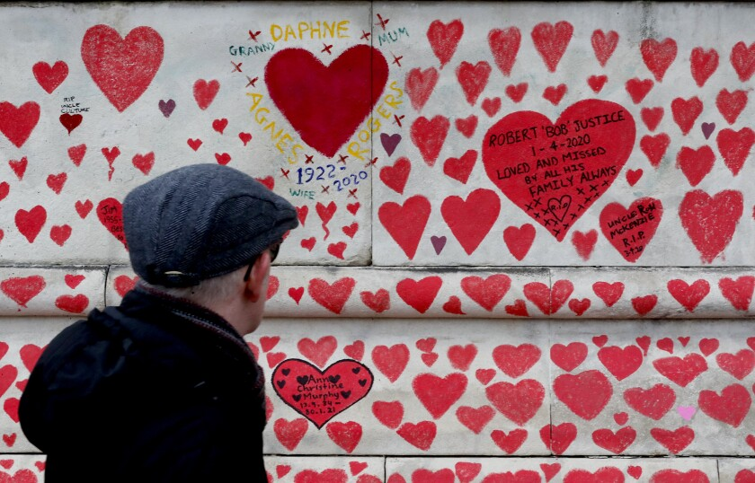 Red hearts cover a concrete wall; some hearts contain writing and dates.