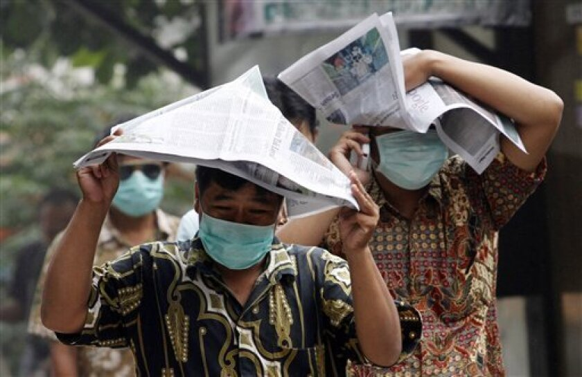 People use newspaper to protect themselves from ash fall from Mount Merapi eruption in Yogyakarta, Indonesia, Friday, Nov. 5, 2010. Blistering gas from Indonesia's most volatile volcano spewed farther than expected Friday, incinerating houses at the edge of the danger zone, triggering chaotic evacuations and pushing the death toll in more than a week to nearly 100. (AP Photo/Achmad Ibrahim)