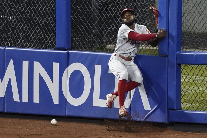 Philadelphia Phillies center fielder Roman Quinn collides with the outfield wall after he missed an RBI double hit by New York Mets' Robinson Chirinos during the sixth inning of a baseball game Saturday, Sept. 5, 2020, in New York. (AP Photo/John Minchillo)