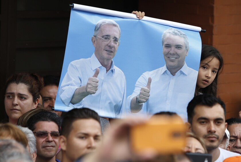 In this June 10, 2018, photo, a girl holds a poster of former President Alvaro Uribe, left, and Ivan Duque, current presidential candidate with the Democratic Center party, during a campaign rally in Armenia, Colombia.