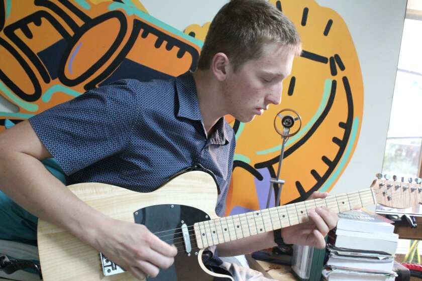 Aidan Fay, who has developed his own functional cockpit to work with a separate flight simulator program, isn't always working. Sometimes, he takes a break to enjoy another hobby: playing the electric guitar (one that he also built).