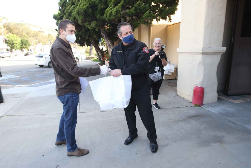 Laguna Beach Fire Chief Michael Garcia, right, is given bags of prepared meals from Frontline Foods' Eric Paine on Monday in observance of International Firefighters Day.
