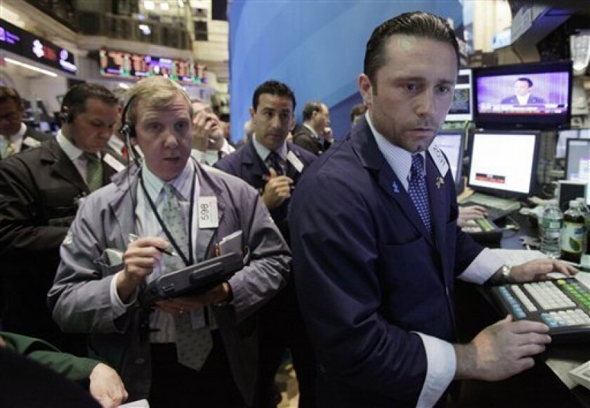 Traders gather around specialist Christopher Gildea, right, at his post on the floor of the New York Stock Exchange Tuesday, May 31, 2011.(AP Photo/Richard Drew)