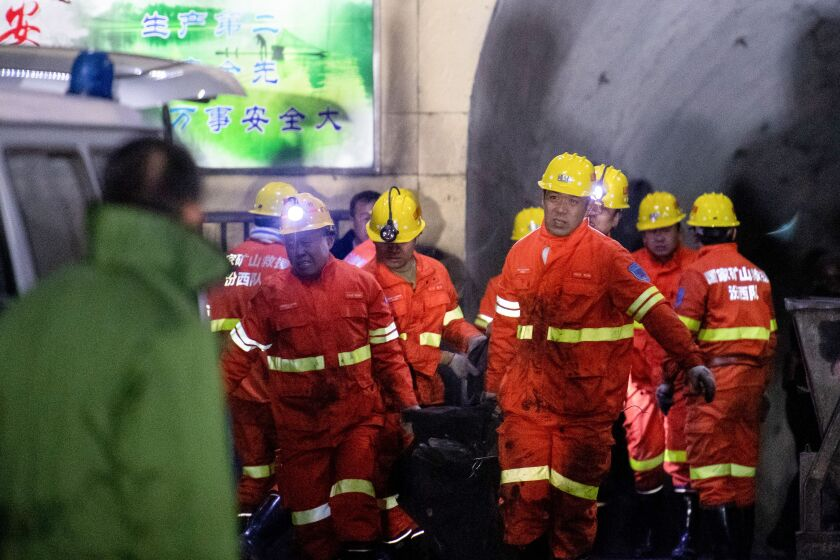 Rescuers carry a victim at the site of a coal mine explosion in China's northern Shanxi province early Tuesday.(AFP/Getty Images)