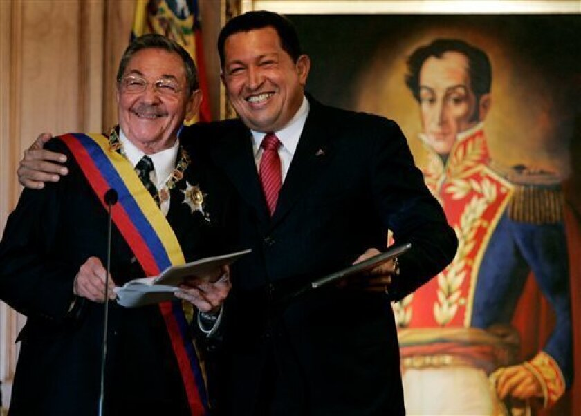Cuba's President Raul Castro, left, stands with Venezuela's President Hugo Chavez at Miraflores presidential palace in Caracas, Saturday, Dec 13, 2008. Castro is in Venezuela on his first international visit as Cuba's leader. Behind is a painting of Venezuela's independence hero Simon Bolivar. (AP Photo/Fernando Llano)