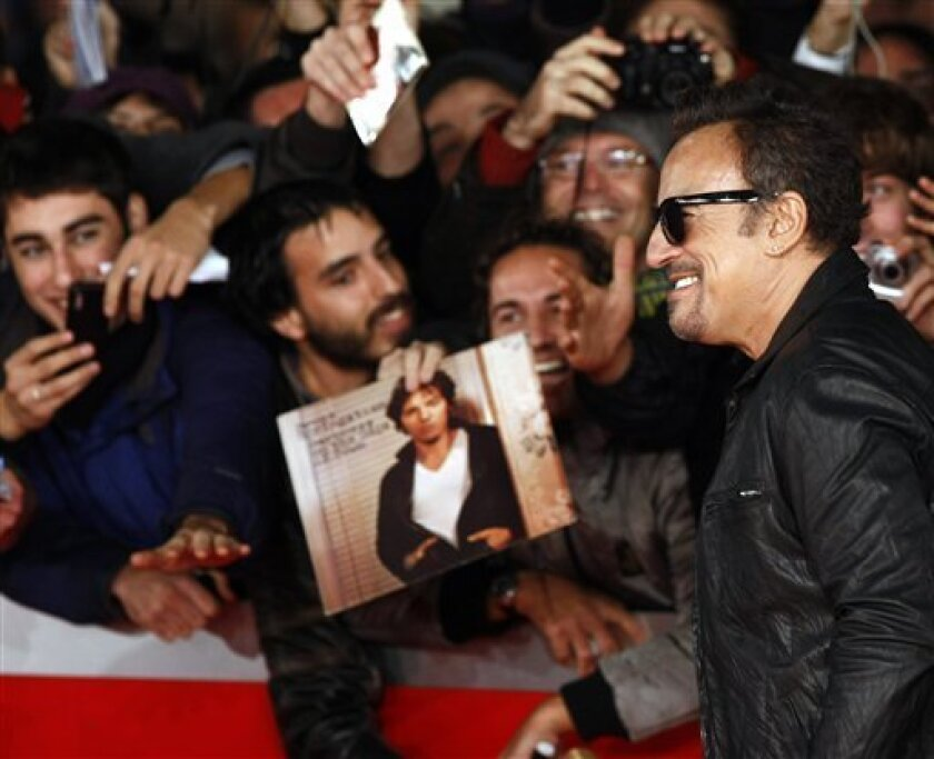 """U.S. artist Bruce Springsteen is cheered by fans as he walks on the red carpet to attend the screening of the movie """"The Promise: The Making of Darkness on the Edge of Town"""" at the Rome Film Festival at Rome's Auditorium, Monday, Nov. 1, 2010. (AP Photo/Pier Paolo Cito)"""