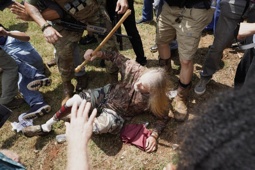 A man falls after being struck during a clash between protesters Saturday in Stone Mountain, Ga.