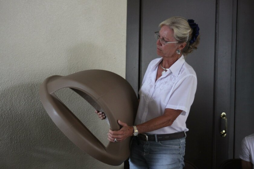 Board member Ann Dynes holds up an example of the proposed sand-colored trash can lids.