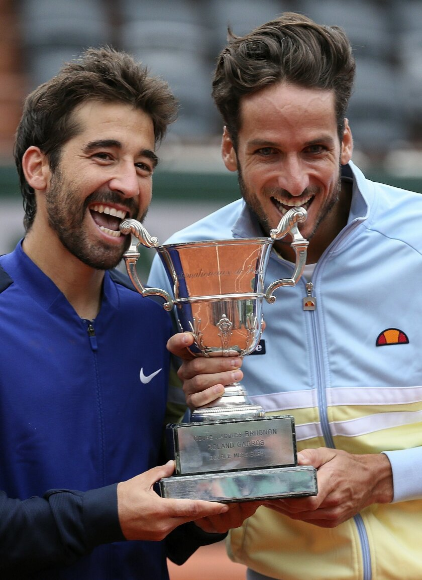 Spanish pair Feliciano Lopez, right, and Marc Lopez bite their trophy after winning the men's doubles final match of the French Open tennis tournament against Bob and Mike Bryan, of the U.S,  at the Roland Garros stadium, Saturday, June 4, 2016 in Paris.  (AP Photo/David Vincent)