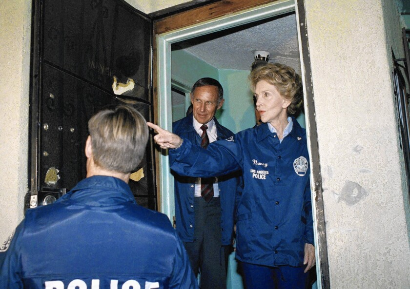 """Nancy Reagan came to L.A. in 1989 to boost her image as an anti-drug crusader. Above, she counts the bullet holes in the front door of a suspected """"rock house"""" in South L.A."""