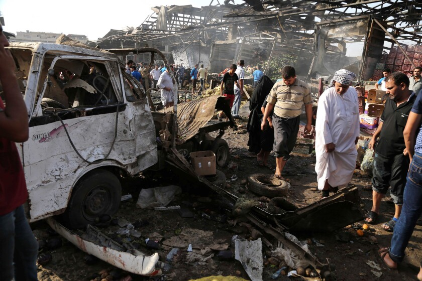 Civilians inspect the scene of an attack in the Jameela market in the crowded Sadr City neighborhood of Baghdad, where a truck bomb detonated Aug. 13.