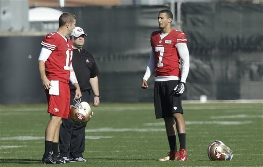 San Francisco 49ers quarterback Colin Kaepernick (7) talks with quarterback Alex Smith (11) and offensive coordinator Greg Roman during practice at an NFL football training facility in Santa Clara, Calif., Friday, Jan. 25, 2013. The 49ers are scheduled to play the Baltimore Ravens in the Super Bowl