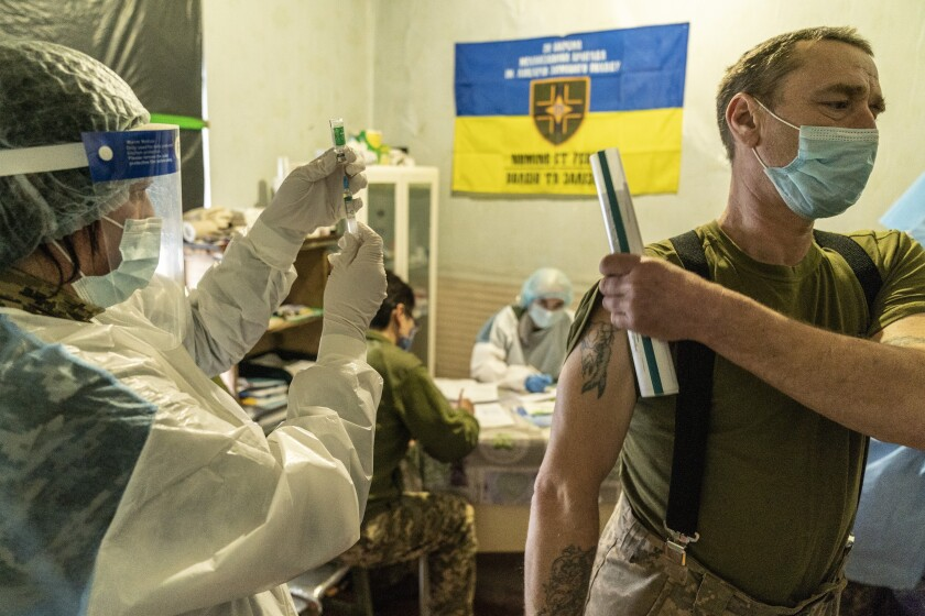 A Ukrainian serviceman prepares to receive a dose of the AstraZeneca COVID-19 vaccine marketed under the name CoviShield at a military base near the front-line town of Krasnohorivka, eastern Ukraine, Friday, March 5, 2021. The country designated 14,000 doses of its first vaccine shipment for the military, especially those fighting Russia-backed separatists in the east. But only 1,030 troops have been vaccinated thus far. In the front-line town of Krasnohorivka, soldiers widely refuse to vaccinate. (AP Photo/Evgeniy Maloletka)