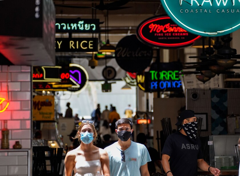 People wear face coverings while walking under neon signs at Grand Central Market in downtown Los Angeles