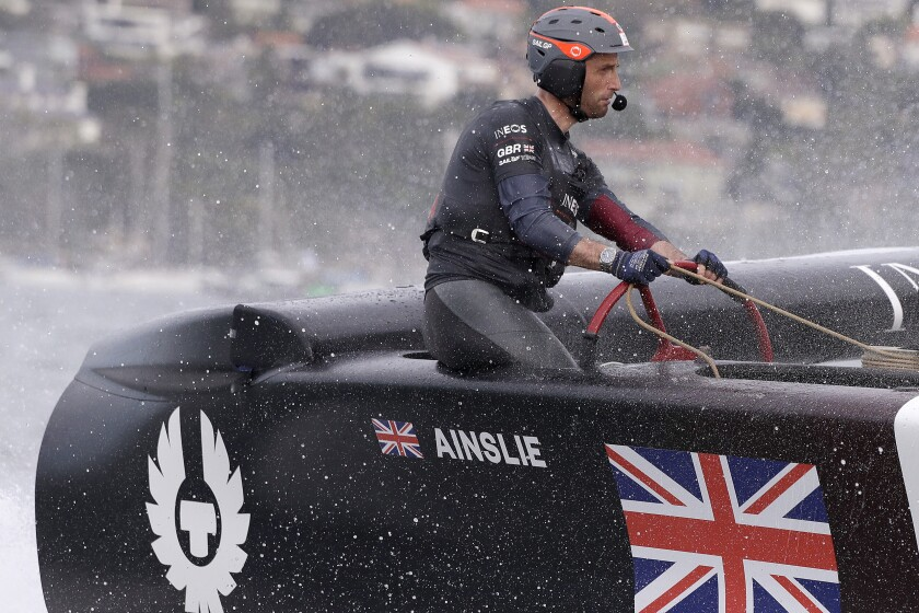 FILE - In this Feb. 29, 2020 file photo, skipper Ben Ainslie steers the boat as the British team crosses the finish line in the second fleet race of the SailGP series in Sydney. America's Cup teams are returning to the water in varying degrees nearly two months after the coronavirus pandemic forced the shutdown of what would have been an impressive global road show. (AP Photo/Rick Rycroft, File)