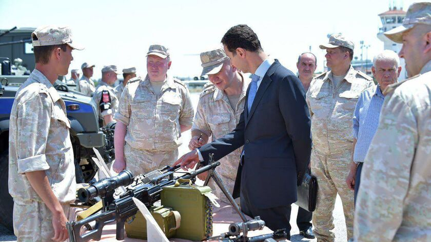 In a handout photo released on the Facebook page of the Syrian presidency on June 27, 2017, President Bashar Assad, center, inspects weapons at the Hmeimim military base in Latakia province, in northwest Syria.
