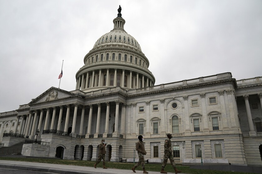 The flag over the Capitol in Washington is flown at half-staff on Friday, as National Guard troops patrol the grounds.