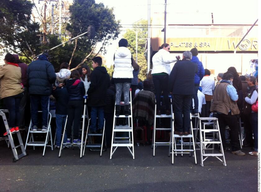 Varios fieles recurrieron a una escalera para poder ver mejor el paso del Pontífice.