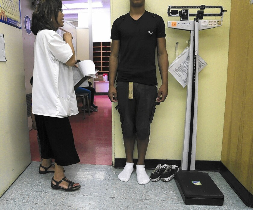 Nurse PractitionerJoyce Yoshimizu weighs and measures a student enrolling in the LAUSD from a foreign country.