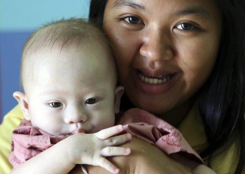 In this photo taken Aug. 3, 2014, Thai surrogate mother Pattaramon Chanbua, a 21-year-old food vendor, poses with Gammy, a nine-month old baby boy who was born with a Down syndrome, at a hospital in Sri Racha, Chonburi province, southeastern Thailand. The case of an Australian couple accused of abandoning their baby with his Thai surrogate mother after discovering the child had Down syndrome, and taking home his healthy twin, has cast unfavorable light on the largely unregulated business of commercial surrogacy. (AP Photo/Apichart Weerawong)