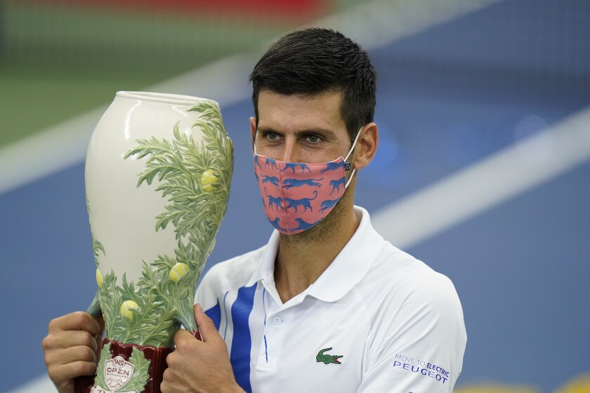 Novak Djokovic holds the championship trophy after winning the Western & Southern Open in New York.