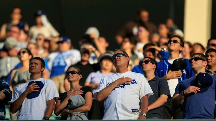 Aficionados durante el himno nacional, en el Dodger Stadium (Jabin Botsford/Los Angeles Times).